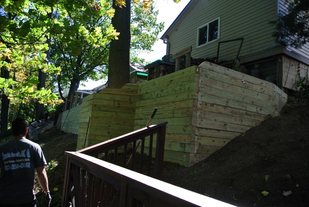 Side view of our sturdy wood retaining wall we built by hand