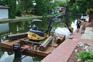 Excavator on a barge on Grand River to install Black Steel Seawall